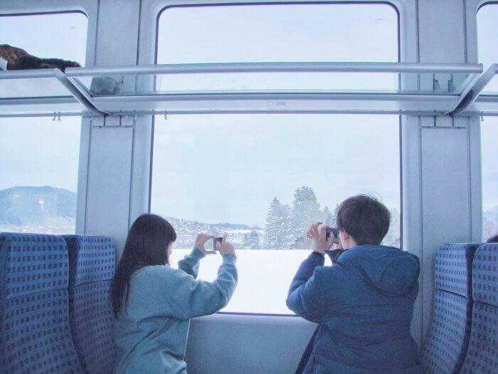 車窓からカメラを向ける男女
