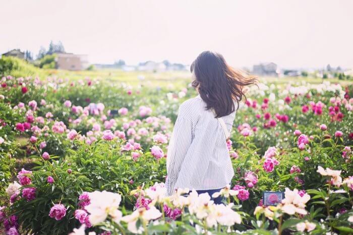 花畑の中でたたずむ女性