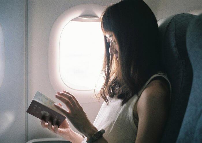 パスポートを機内で確認する女性