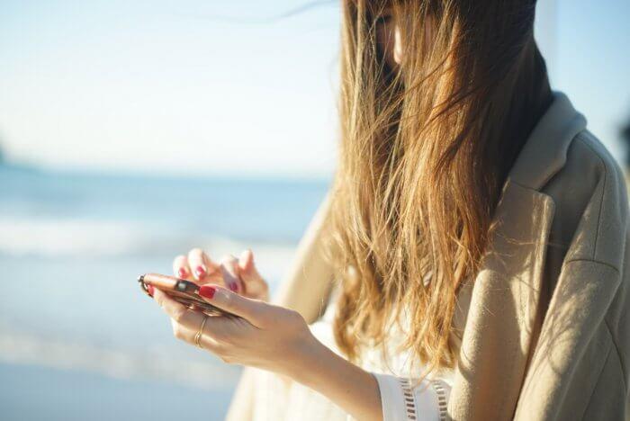 スマホを操作する髪の長い女性