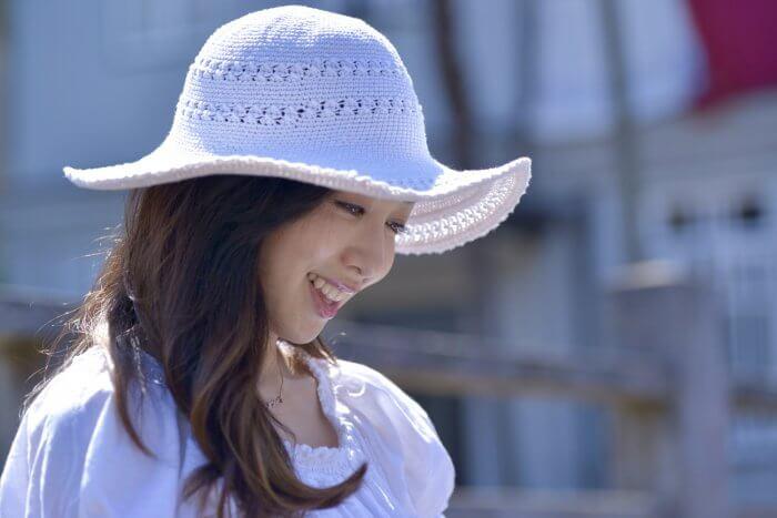 笑顔で少し俯く白い帽子をかぶった女性