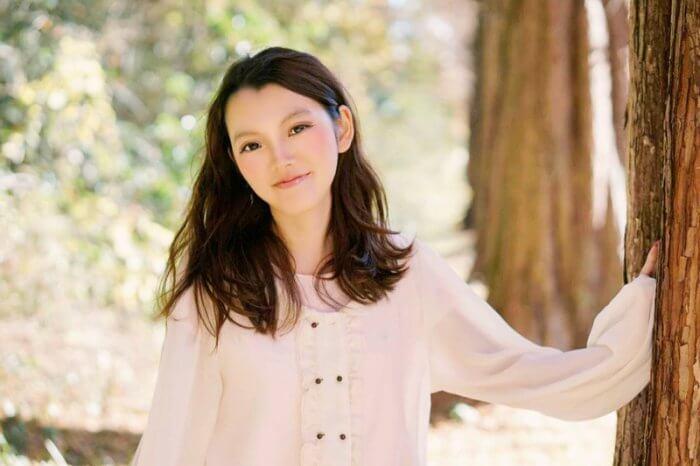 木の横に立つ清潔感のある若い女性