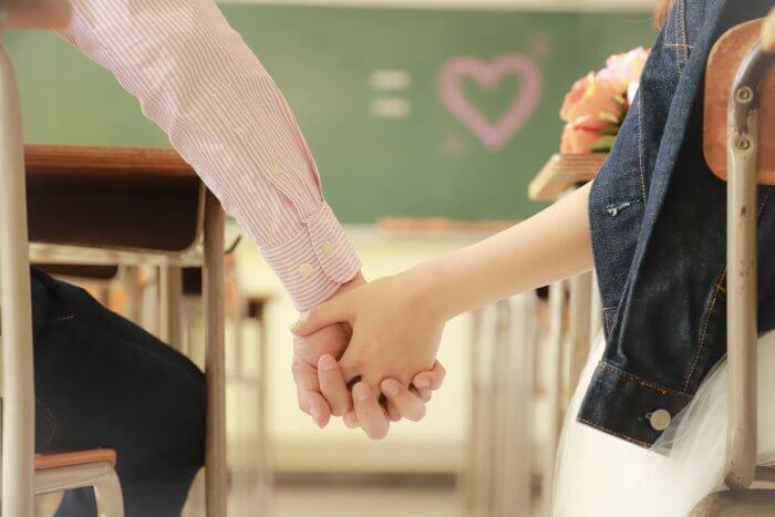 教室で手を握るカップル