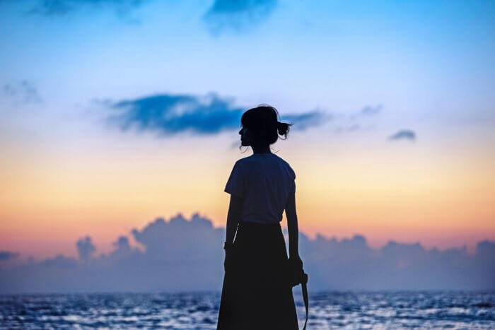 夕暮れの海辺にたたずむ女性