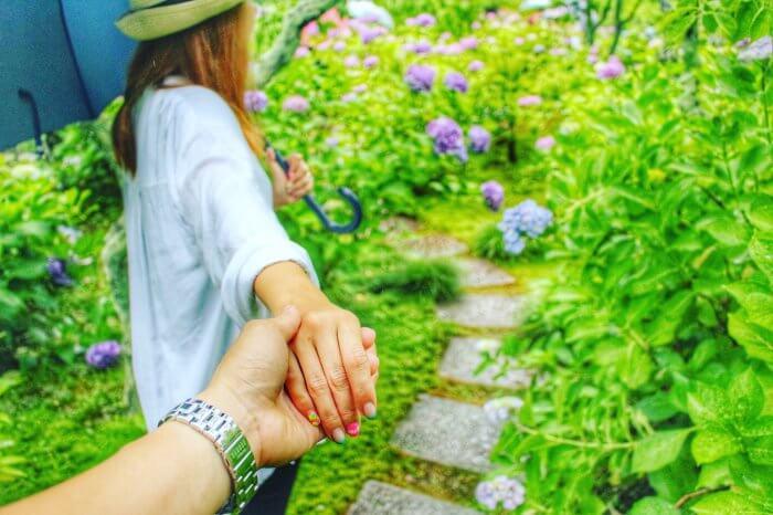 細い道を彼の手を握りながら歩く女性