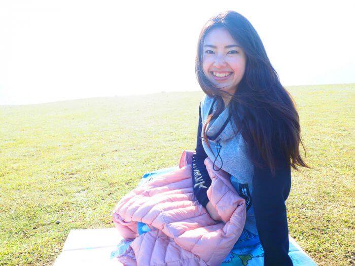 芝生に座ってやわらかく微笑む女性