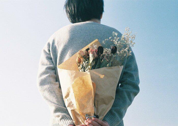 背中に花束を隠す男性