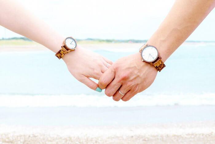 手を繋ぐ腕時計をした男女