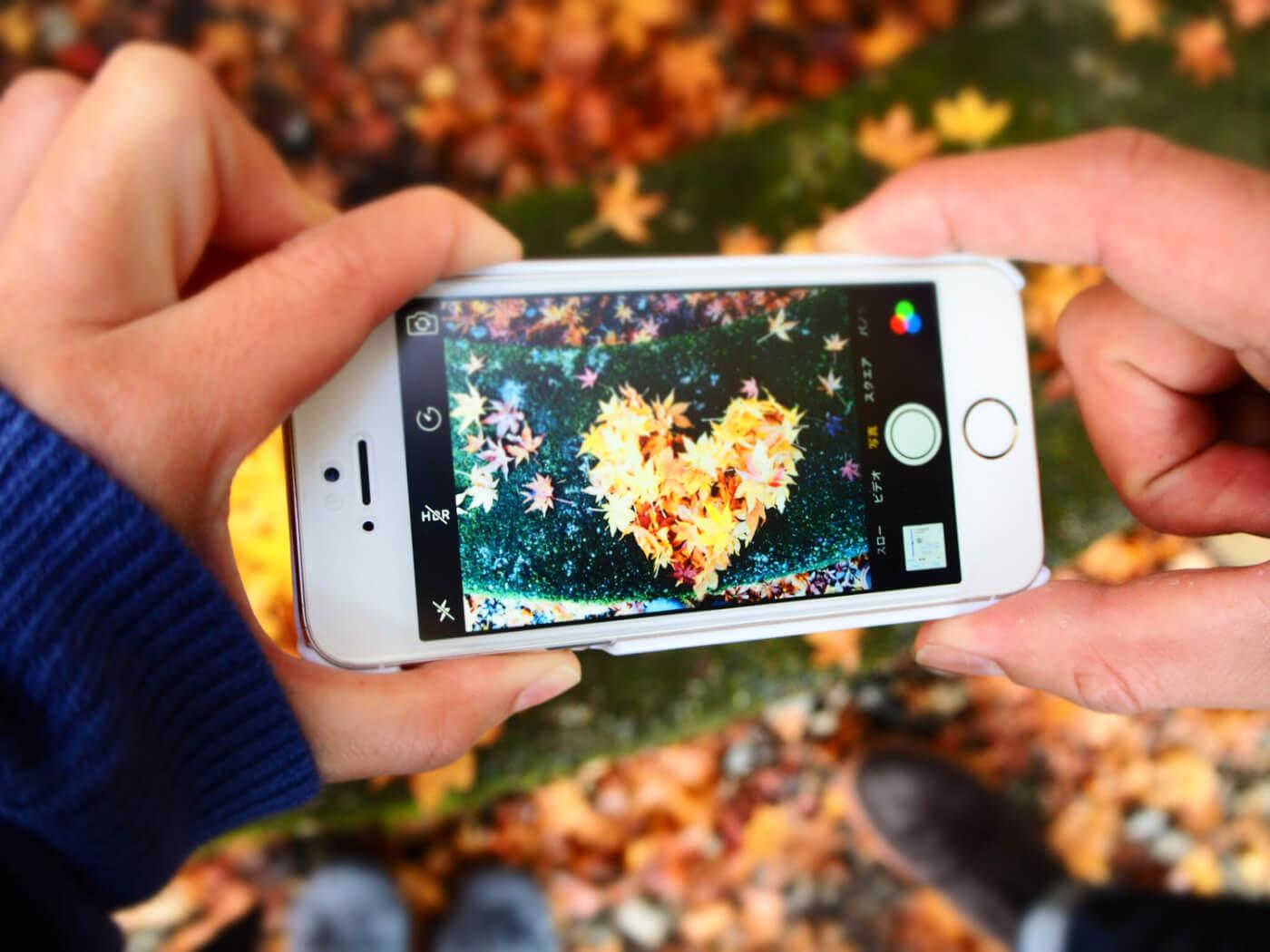 スマホで紅葉の写真を撮る手元