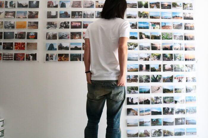 規則正しく並んだ写真を眺める男性