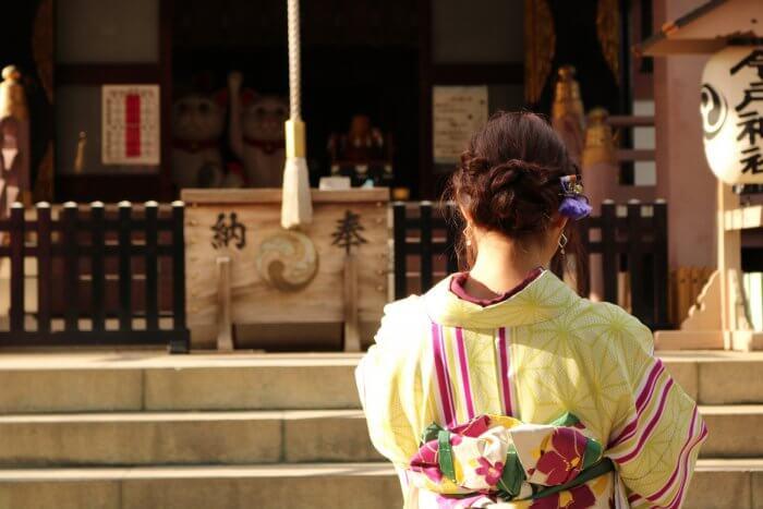 浴衣姿で神社に参拝する女性