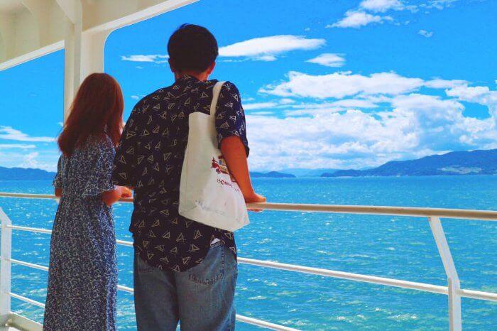 船から海を眺める男女