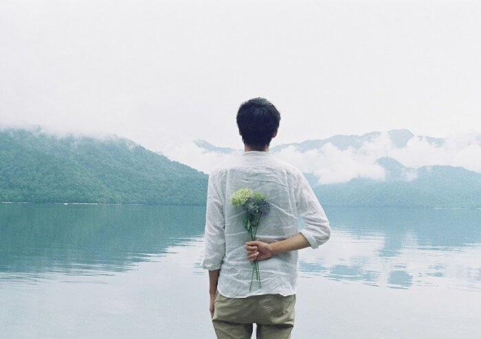 花を持った男性の後ろ姿