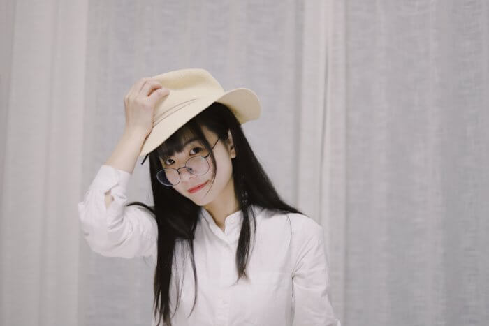 帽子に触れる女性