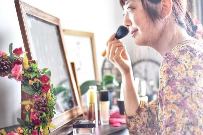 鏡の前でメイクしている女性