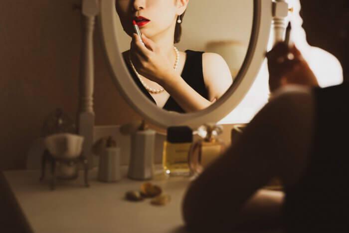 鏡の前で口紅を塗る女性