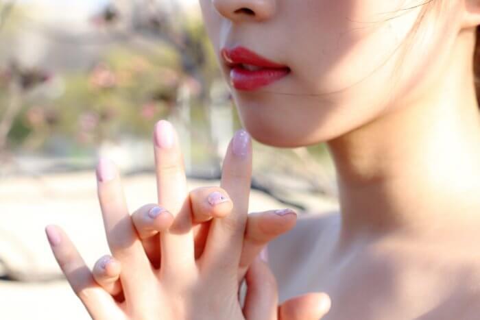 女性の口元と指先