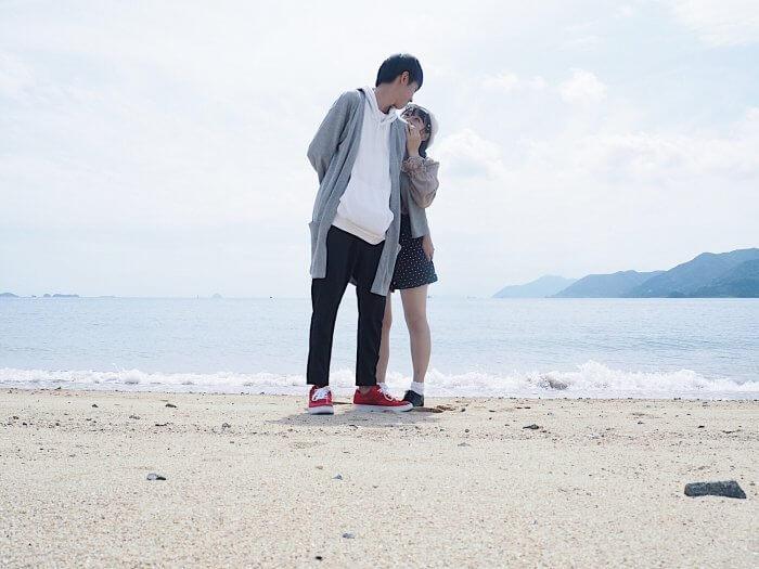 浜辺に立つカップル