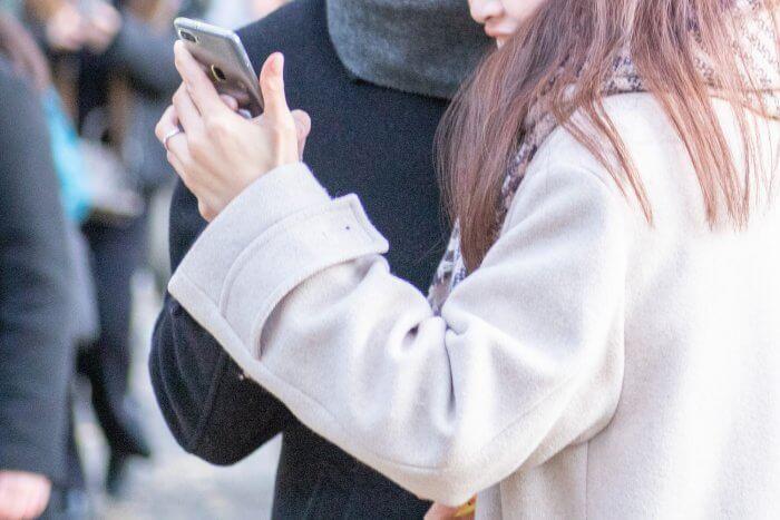 スマートフォンをのぞき込む男女