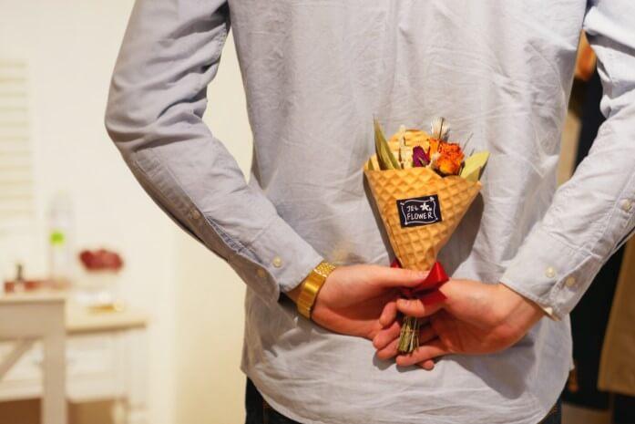 花を隠し持つ男性