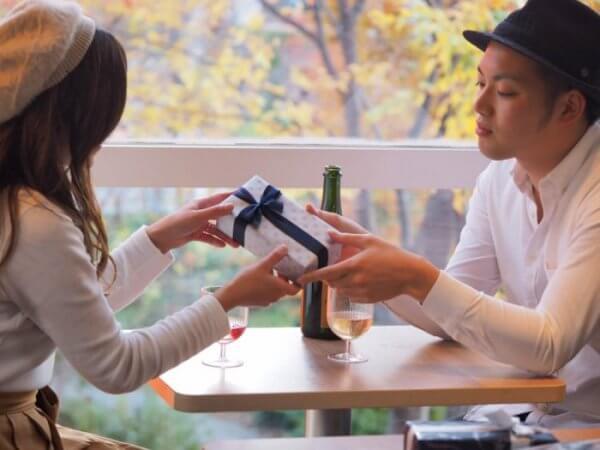 彼氏にプレゼントを渡す女性