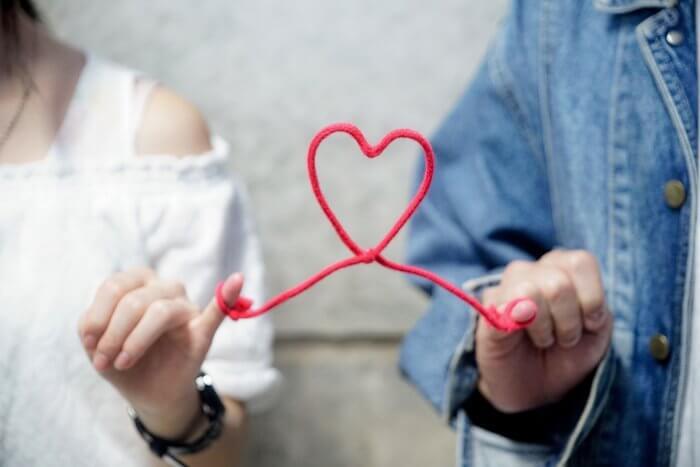 小指を赤い糸で結ばれたカップル