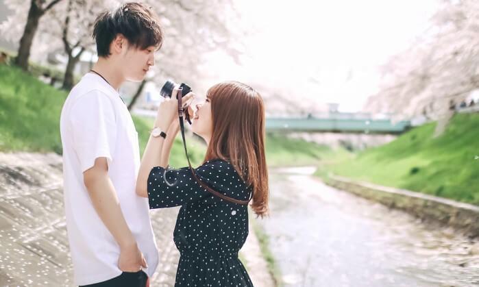 桜の側で写真を撮るカップル
