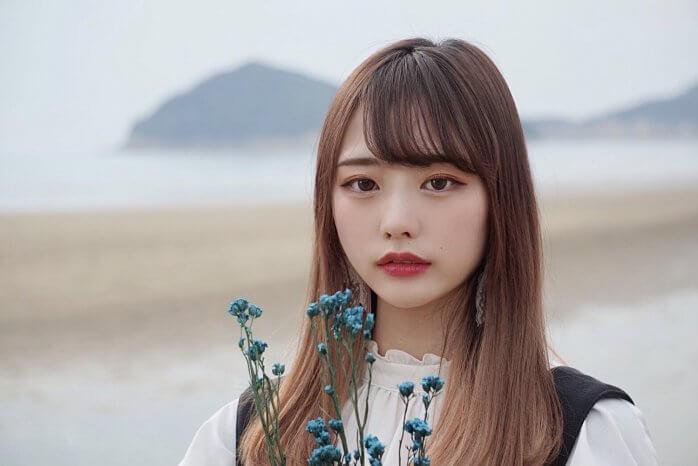 砂浜で青い花を持つ女性