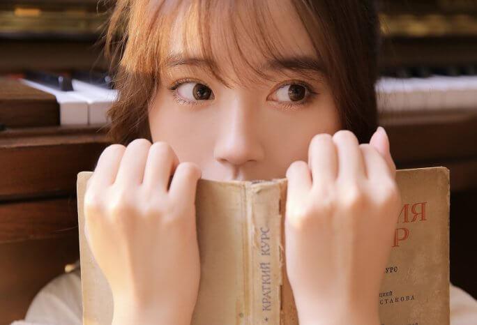 本の上から顔を出す女性